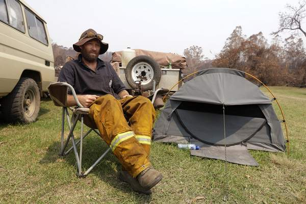Volunteer firefighter Ash Graham camps on the lawn near the fire station at Nerrigundah, Australia, Monday, Jan. 13, 2020, since losing his house and his dog when a wildfire ripped through the town on New Year's Eve. (AP Photo/Rick Rycroft)