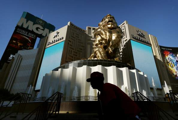 FILE - In this Aug. 3, 2015, file photo, a man rides his bike past the MGM Grand hotel and casino in Las Vegas. (AP Photo/John Locher, File)