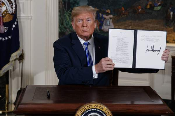 FILE - In this May 8, 2018 file photo, President Donald Trump shows a signed Presidential Memorandum after delivering a statement on the Iran nuclear deal from the Diplomatic Reception Room of the White House. (AP Photo/Evan Vucci, File)