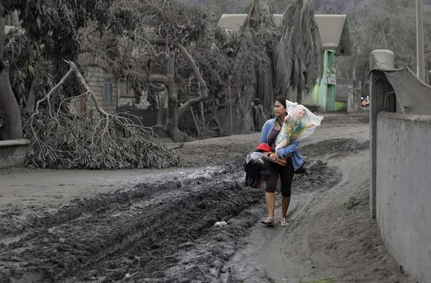 Leila de Castro carries a statue of the baby Jesus which she recovered from the house of her sister as she walks on a road covered with volcanic ash in Boso-Boso, Batangas province, southern Philippines on Tuesday, Jan. 14, 2020. (AP Photo/Aaron Favila)