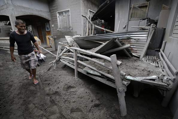 A resident looks at a structure that was damaged from volcanic ash at Laurel, Batangas province, southern Philippines on Tuesday, Jan. 14, 2020. (AP Photo/Aaron Favila)