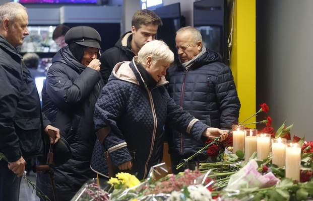 Relatives of one of the flight crew members of the Ukrainian 737-800 plane that crashed on the outskirts of Tehran, stand at a memorial inside Borispil international airport outside Kyiv, Ukraine, Saturday, Jan. 11, 2020. (AP Photo/Efrem Lukatsky)