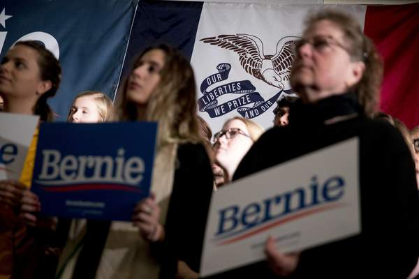 Members of the audience hold campaign posters in front of the Iowa state flag before Democratic presidential candidate Sen. Bernie Sanders, I-Vt., arrives at a climate rally with the Sunrise Movement at The Graduate Hotel, Sunday, Jan. 12, 2020, in Iowa City, Iowa. (AP Photo/Andrew Harnik)