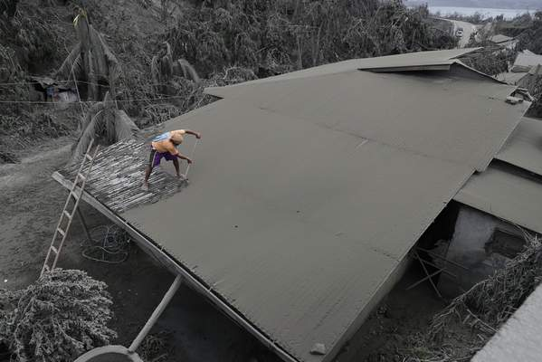 A resident clears volcanic ash from his roof in Laurel, Batangas province, southern Philippines on Tuesday, Jan. 14, 2020. (AP Photo/Aaron Favila)