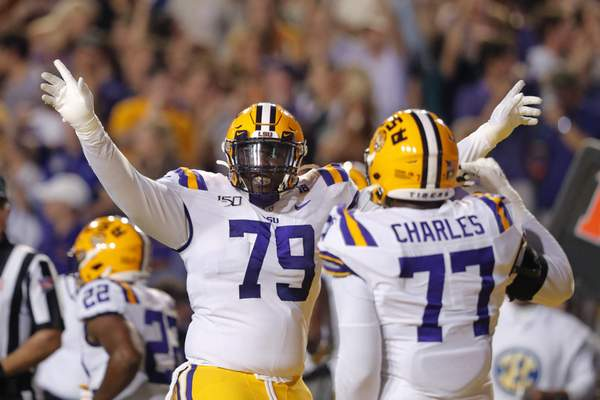 LSU center Lloyd Cushenberry III (79) and offensive tackle Saahdiq Charles (77) celebrate an LSU touchdown during the first half of the team's NCAA college football game against Texas A&M in Baton Rouge, La., Saturday, Nov. 30, 2019. (AP Photo/Gerald Herbert)