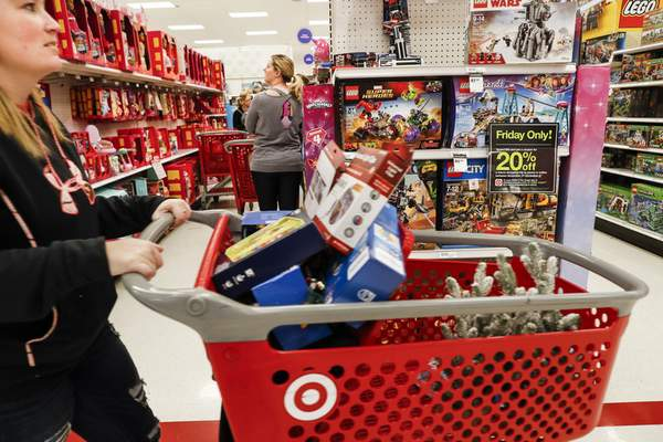 FILE- In this Nov. 23, 2018, file photo shoppers browse the aisles during a Black Friday sale at a Target store in Newport, Ky. (AP Photo/John Minchillo, File)