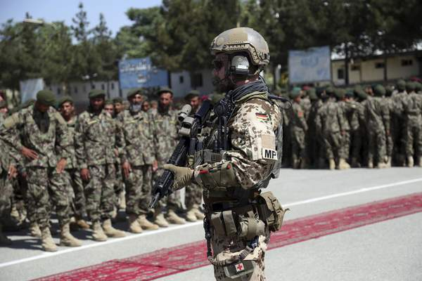 FILE- In this Wednesday, July 10, 2019 file photo, a German soldier with NATO forces stands guard during the graduation ceremony of newly Afghan National Army soldiers after a 3-month training program at the Afghan Military Academy in Kabul, Afghanistan. (AP Photo/Rahmat Gul, File)