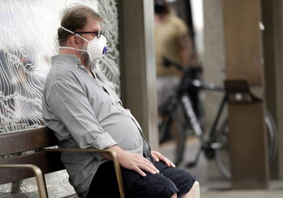 FILE - In this Jan. 2, 2020, file photo, a commuter wears a mask as smoke shrouds the Australian capital of Canberra, Australia. (AP Photo/Mark Baker, File)