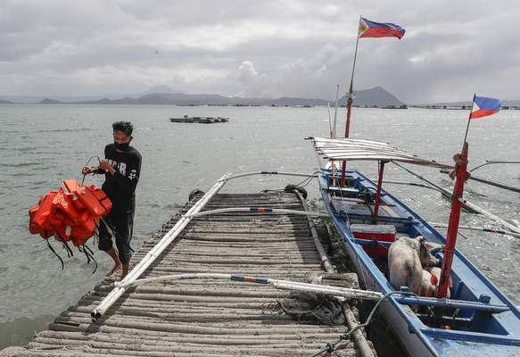 In this Jan. 14, 2020, photo, Christian Morales carries life vests beside his pigs which they rescued across the lake in Talisay, Batangas province, southern Philippines, as Taal volcano continues to spew ash. (AP Photo/Aaron Favila)