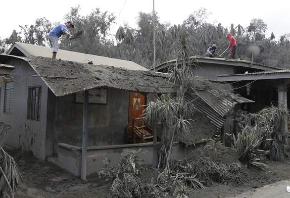 In this Jan. 14, 2020, photo, residents clean their roofs from volcanic ash in Laurel, Batangas province, southern Philippines, as Taal volcano continues to spew ash. (AP Photo/Aaron Favila)