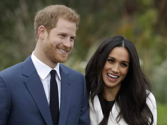FILE - In this Monday Nov. 27, 2017 file photo, Britain's Prince Harry and his fiancee Meghan Markle pose for photographers during a photocall in the grounds of Kensington Palace in London. (AP Photo/Matt Dunham, File)