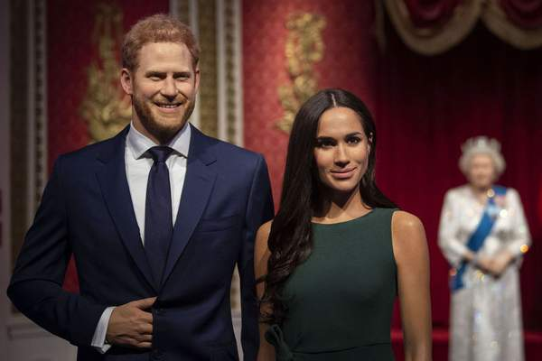 The figures of Britain's Prince Harry and Meghan, Duchess of Sussex, left, are moved from their original positions next to Queen Elizabeth II, Prince Philip and Prince William and Kate, Duchess of Cambridge, at Madame Tussauds in London, Thursday Jan. 9, 2020. (Victoria Jones/PA via AP)