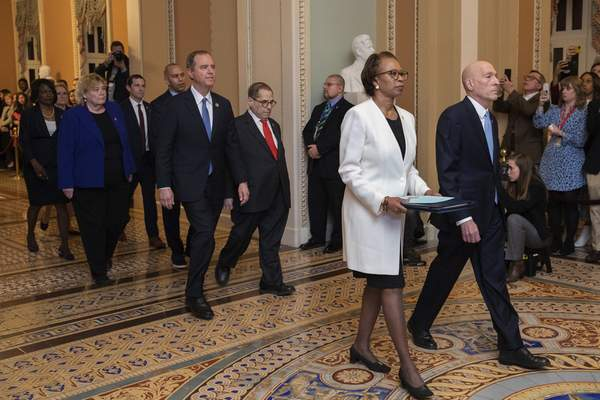 Associated Press  House Sergeant at Arms Paul Irving and Clerk of the House Cheryl Johnson carry the articles of impeachment against President Donald Trump to Secretary of the Senate Julie Adams on Capitol Hill in Washington, Wednesday.