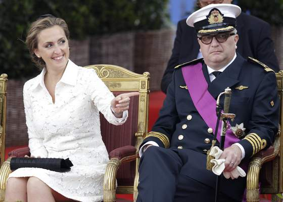 FILE - In this Monday, July 21, 2014 file photo, Belgium's Prince Laurent and his wife Claire watch a military parade on Belgian National Day, in front of the Royal Palace in Brussels. As the British royal family wrestles with the future roles of Prince Harry and his wife Meghan, it could look to Europe for examples of how princes and princesses have tried to carve out careers away from the pomp and ceremony of their families' traditional duties. Prince Laurent, the brother of Belgium's King Philippe, has long struggled with his royal role and obligations that come with his annual tax payer-funded endowment. (AP Photo/Yves Logghe, File)