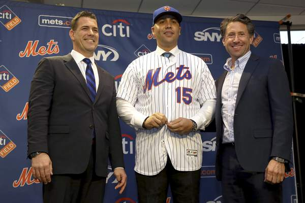 FILE - In this Nov. 4, 2019, file photo, new New York Mets manager, Carlos Beltran, center, poses for a picture with general manager Brodie Van Wagenen, left, and Mets COO Jeff Wilpon during a baseball news conference at Citi Field in New York. (AP Photo/Seth Wenig, File)