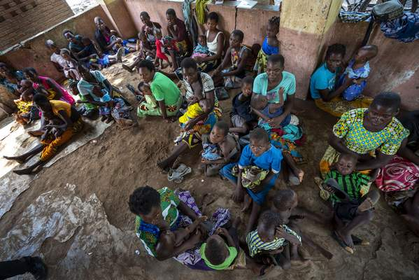 In this photo taken Wednesday, Dec. 11, 2019, residents of the Malawi village of Tomali wait to have their young children become test subjects for the world's first vaccine against malaria. (AP Photo/Jerome Delay)