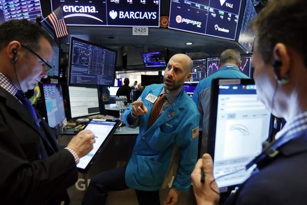 FILE - In this Jan. 10, 2020, file photo specialist Meric Greenbaum, center, works at his post on the floor of the New York Stock Exchange. (AP Photo/Richard Drew, File)