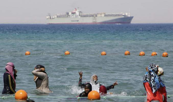 FILE - In this Sunday, Aug. 9, 2015 file photo, a ship crosses the Gulf of Suez towards the Red Sea as holiday-makers swim in Suez, 127 kilometers (79 miles) east of Cairo, Egypt. (AP Photo/Amr Nabil, File)