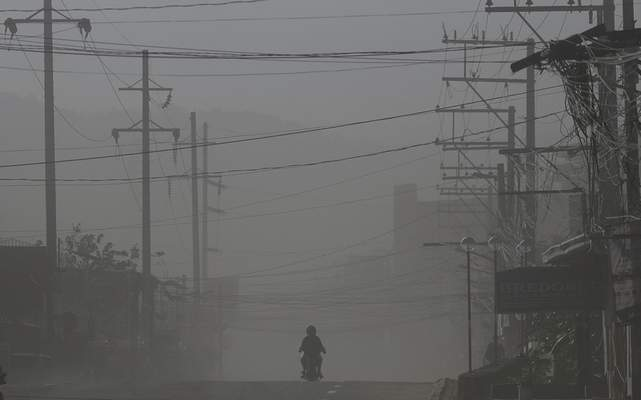 A motorcycle rider drives along a street as wind blows volcanic ash from Taal volcano at a deserted town in Lemery, Batangas province, southern Philippines on Thursday Jan. 16, 2020. (AP Photo/Aaron Favila)