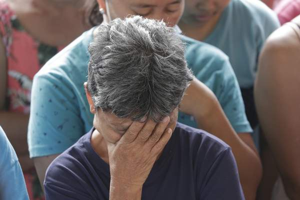 A woman reacts during prayers before the distribution of relief goods at an evacuation center at Santa Teresita, Batangas province, southern Philippines on Thursday Jan. 16, 2020. (AP Photo/Aaron Favila)