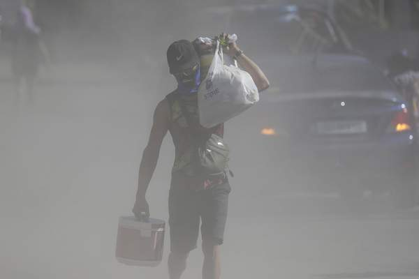 A man walks the his belongings through clouds of ash kicked up on a road as authorities enforced total evacuation of residents living near Taal volcano in Agoncillo town, Batangas province, southern Philippines on Thursday Jan. 16, 2020. (AP Photo/Aaron Favila)