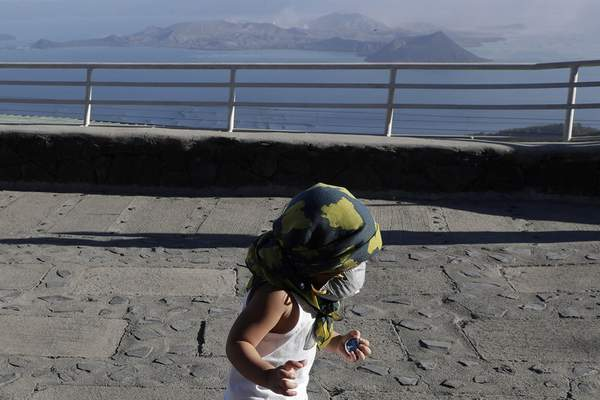 A boy wears a face mask as he plays with Taal volcano in the rear from Tagaytay, Cavite province, southern Philippines on Thursday Jan. 16, 2020. (AP Photo/Aaron Favila)