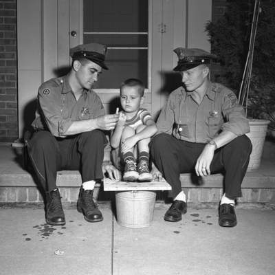 June 22, 1954: Bill Leming tells police officers about his finger, which was bitten by a squirrel. The officers, Albert Bragalone, left, and Don Schoenherr, chased the squirrel for more than an hour before capturing it and placing it in a bucket, which is under the board Bill has his feet on. (Journal Gazette file photo)
