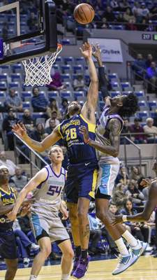 Mike Moore | The Journal Gazette  Mad Ants forward Ben Moore and Swarm forward Jalen McDaniels go up for a rebound in the first quarter at Memorial Coliseum on Friday.