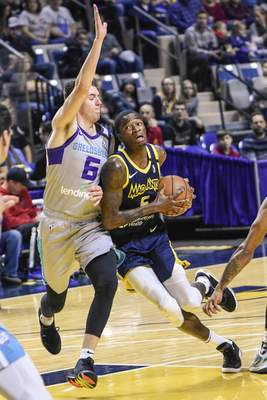 Mike Moore | The Journal Gazette Mad Ants guard Edmond Sumner drives to the basket in the first quarter against Greensboro at Memorial Coliseum on Friday.