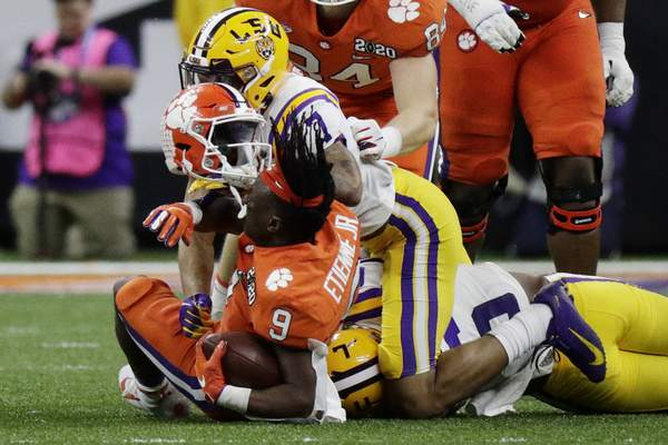 LSU safety Grant Delpit knocks the helmet off Clemson running back Travis Etienne during the first half of a NCAA College Football Playoff national championship game Monday, Jan. 13, 2020, in New Orleans. (AP Photo/Sue Ogrocki)