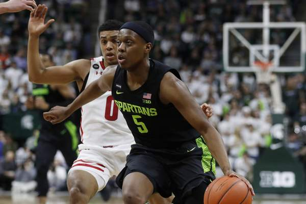 Associated Press Michigan State guard Cassius Winston drives past Wisconsin guard D'Mitrik Trice on Friday night.