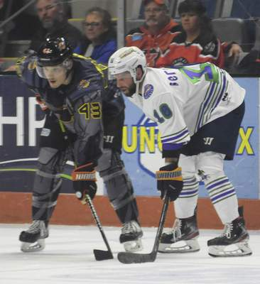 Katie Fyfe | The Journal Gazette  Komets defenseman Gabriel Verpaelst and Toledo forward Shane Berschbach get ready for a faceoff during the second period at Memorial Coliseum on Saturday.