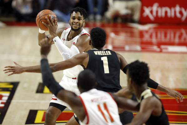 Maryland forward Donta Scott, top, looks for an open teammate against Purdue during the first half of an NCAA college basketball game, Saturday, Jan. 18, 2020, in College Park, Md. (AP Photo/Julio Cortez)