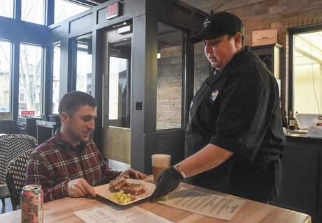 Michelle Davies | The Journal Gazette Tab Mathis, deli connoisseur at Antonuccio's Italian Market, serves lunch to Josh Jeffrey of Fort Wayne, who was dining in the market for the first time.