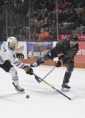Brady Shaw, right, passes the puck while Toledo's Troy Loggins defends Saturday at Memorial Coliseum.