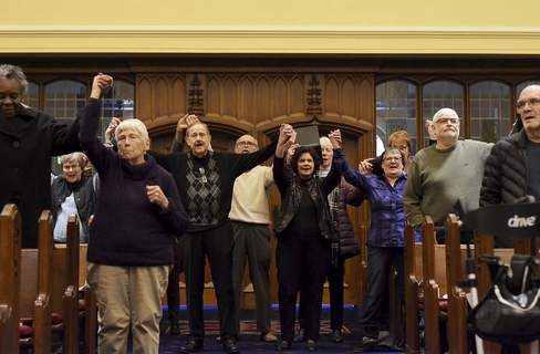 Attendees hold hands during Sunday's concert at Plymouth Congregational Church. Today is Martin Luther King Jr. Day.