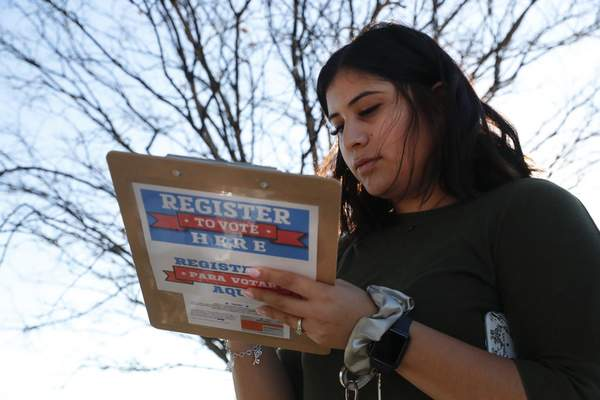 Karina Shumate, 21, a college student studying stenography, fills out a voter registration form in Richardson, Texas, Saturday, Jan. 18, 2020. (AP Photo/LM Otero)