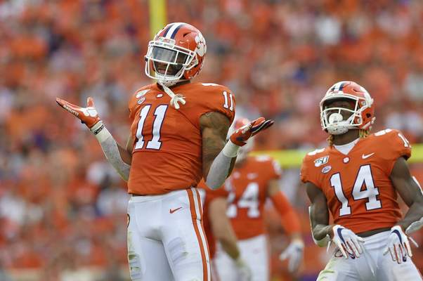 FILE - In this Oct. 12, 2019, file photo, Clemson's Isaiah Simmons (11) and Denzel Johnson react after making a defensive play during the first half of an NCAA college football game against Florida State, in Clemson, S.C.  (AP Photo/Richard Shiro, File)