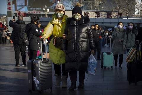 China Outbreak Travelers wear face masks as they walk outside of the Beijing Railway Station in Beijing, Monday, Jan. 20, 2020. (AP Photo/Mark Schiefelbein) (Mark Schiefelbein