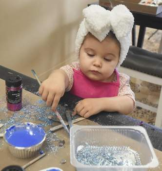 Michelle Davies | The Journal Gazette Harper Western, 2, from Columbia City, makes a glittered Popsicle stick snowflake at Monday's January Preschool Craft Club at Well Grounded Cafe in Huntertown.