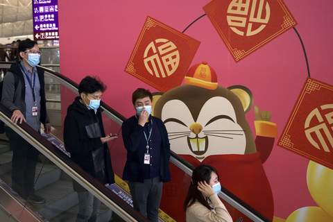 Hong Kong Outbreak Associated Press People wear masks as they ride an escalator Tuesday at Hong Kong International Airport. Airports across the world have tightened screenings in the aftermath of a deadly virus outbreak circulating in China. (Ng Han GuanSTF)