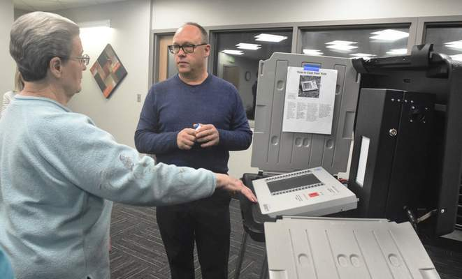 Michelle Davies | The Journal Gazette Steve Shamo, a trainer with MicroVote, explains how devices added to voting machines will improve voting security.