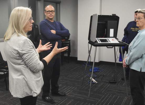 Michelle Davies | The Journal Gazette Beth Dlug, Director of Elections, and Steve Shamo, with MicroVote, explain how a new voting machine meets the requirement for Indiana voting machines to have VVPATS (Voter Verifiable Paper Audit Trails).