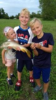 Sawyer Hackett, left, Cooper Hackett, with the large fish, and Chance Hackett, with the bluegill, caught these fish at their grandparents' house on Bass Road in August. The Hacketts, from Greenwood, always fish in the pond behind the house when they visit.