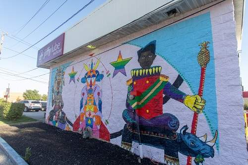Courtesy: Jiffy Lube  Artist: ISH (Ismael Muhammad Nieves) with apprentices Matthew Cooper and Jamahl Crouch Address: 8580 N. Michigan Rd, at 86th St. Neighborhood: Northwest Indianapolis  The three figures in the mural represent the fact that this Jiffy Lube location was the third one opened in Indiana, nearly thirty years ago.