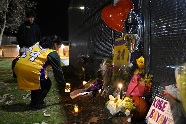 Christina Espinoza places a candle inside a small memorial made in remembrance of former basketball player Kobe Bryant in Calabasas, Calif., Sunday, Jan. 26, 2020, following reports of his death in a helicopter crash in southern California. (AP Photo/Kelvin Kuo)