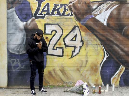 A man pays respects at a mural of Kobe Bryant in an alley in downtown Los Angeles after word of the Lakers star's death in a helicopter crash, Sunday, Jan. 26, 2020. (AP Photo/Matt Hartman)