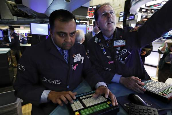 Specialists Dilip Patel, left, and Glenn Carell work at a post on the floor of the New York Stock Exchange, Monday, Jan. 27, 2020. Stock tumbled at the open on Wall Street following a sell-off in markets in Europe and Japan as investors grow more concerned about the potential economic impact of an outbreak of a deadly coronavirus. (AP Photo/Richard Drew)