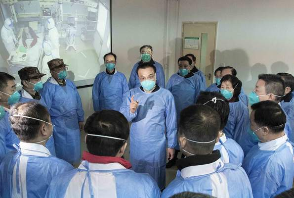 In this photo released by China's Xinhua News Agency, Chinese Premier Li Keqiang, center, speaks with medical workers at Wuhan Jinyintan Hospital in Wuhan in central China's Hubei province, Monday, Jan. 27, 2020. (Li Tao/Xinhua via AP)
