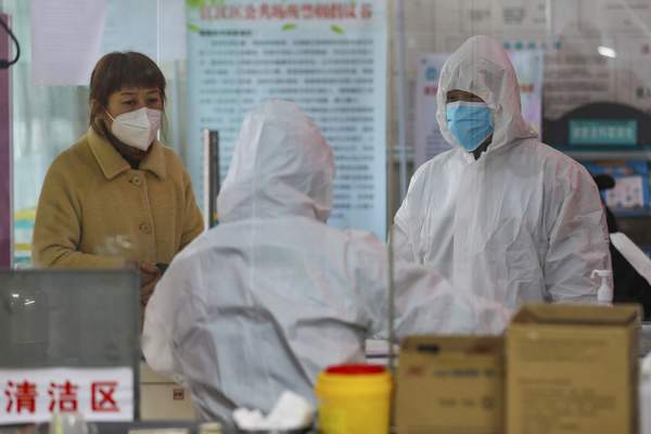 Medical workers in protective gear talk with a woman suspected of being ill with a coronavirus at a community health station in Wuhan in central China's Hubei Province, Monday, Jan. 27, 2020. (Chinatopix via AP)